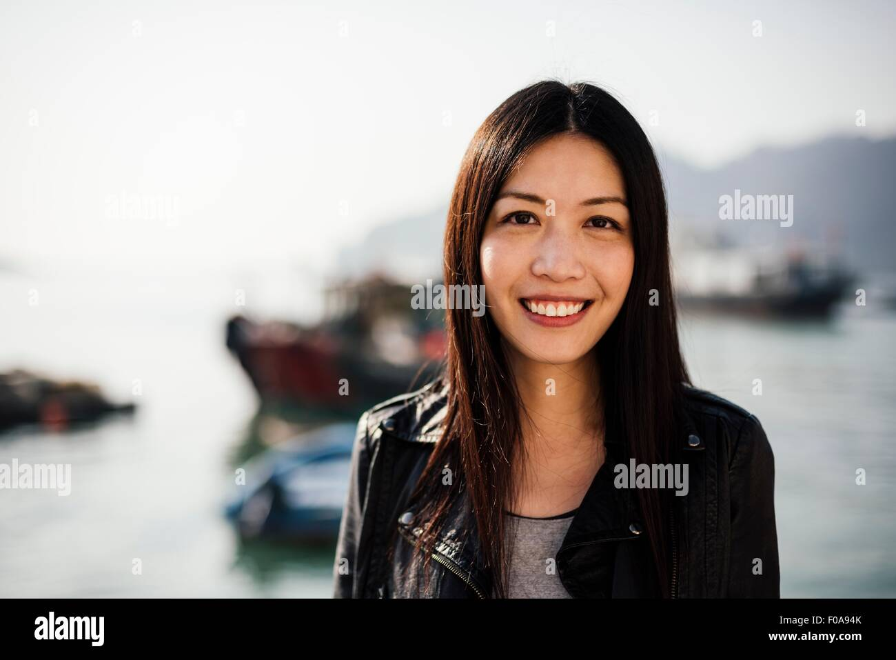 Portrait of young woman in front of boats on water, looking at camera smiling - Stock Image