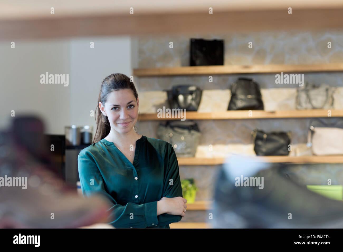 Portrait of proud female sales assistant in shoe shop - Stock Image