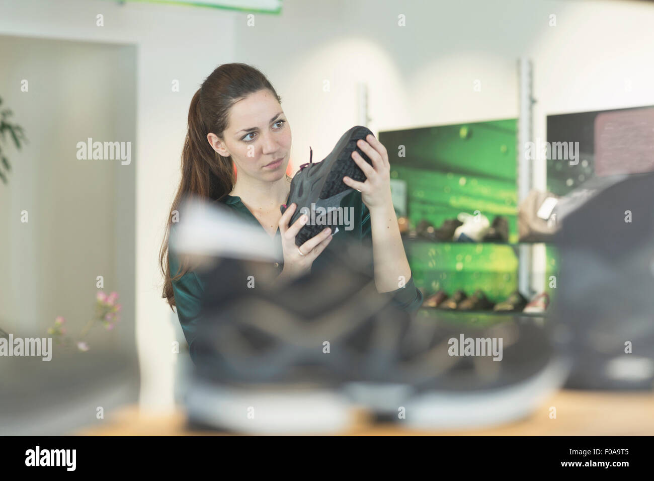 Young female shopper inspecting trainer in shoe shop - Stock Image