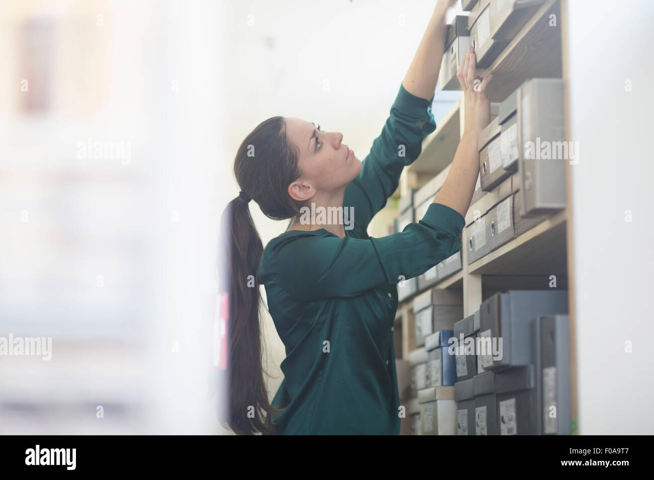 Female sales assistant reaching for shoe box in shoe shop stockroom - Stock Image