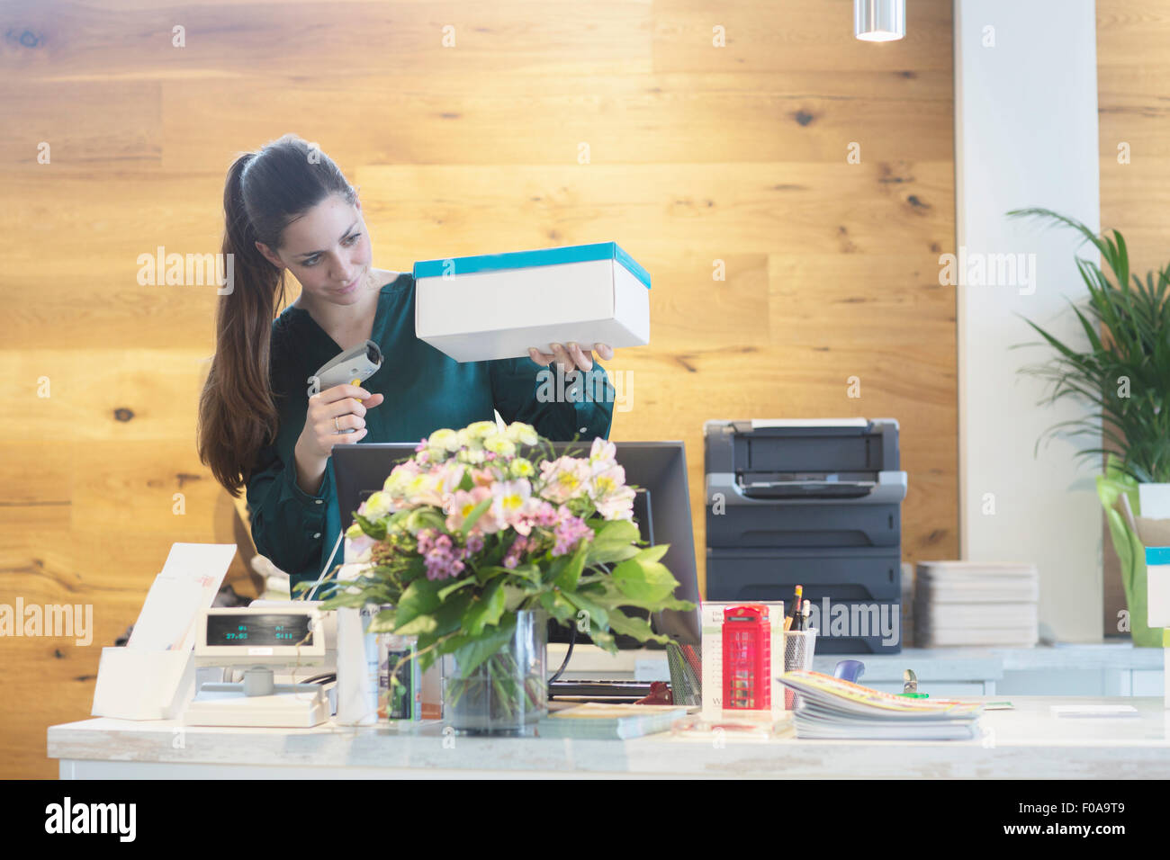 Female sales assistant using barcode reader on shoe box in shoe shop - Stock Image