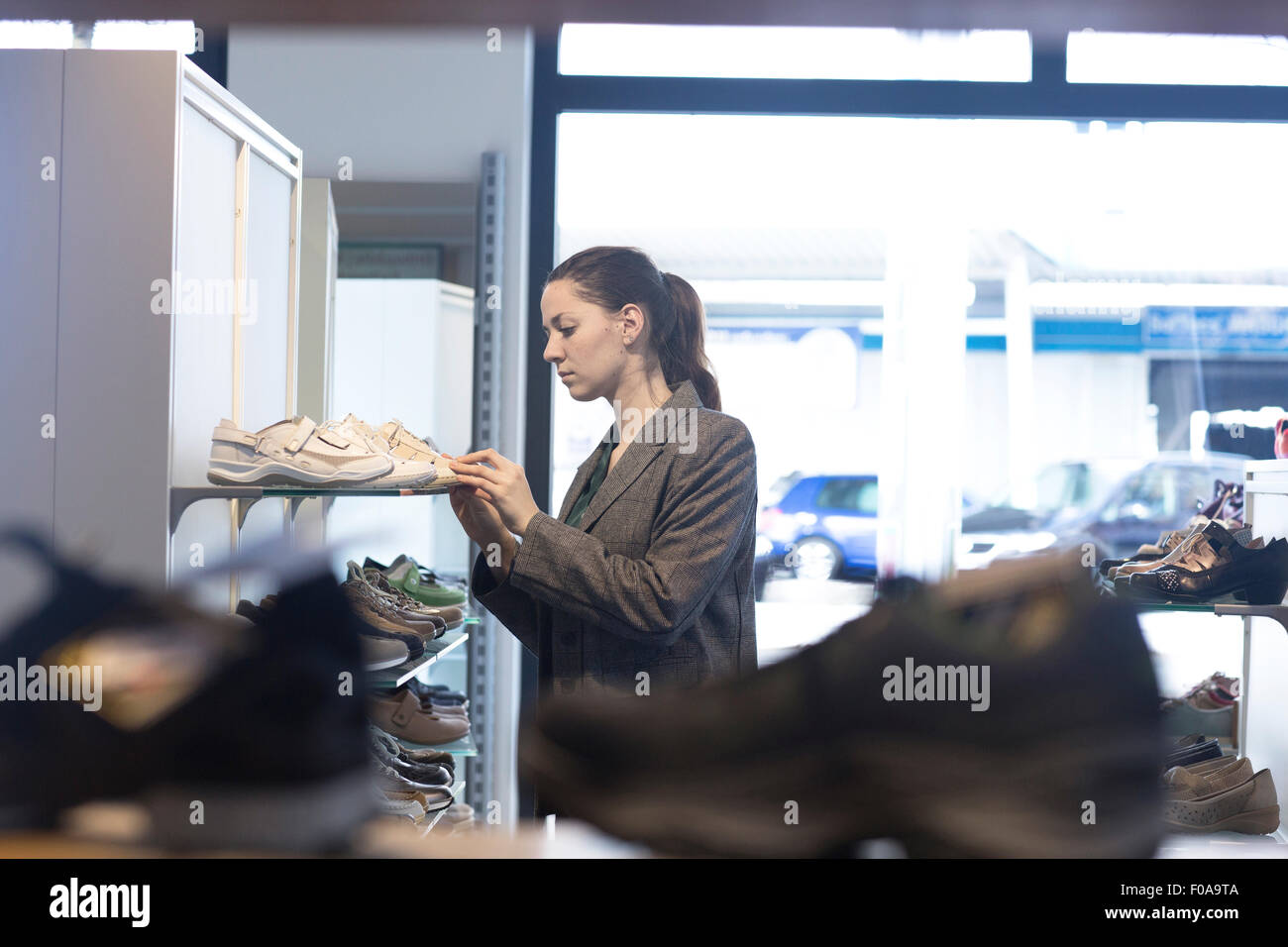Young female shopper selecting trainer in shoe shop - Stock Image