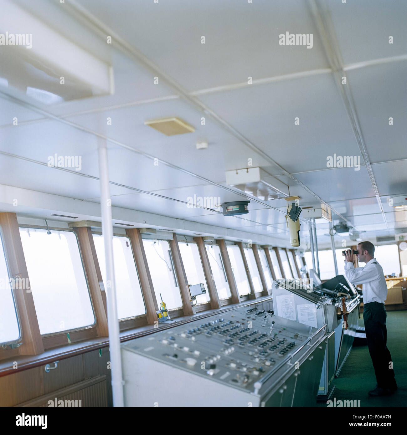 Sailor using binoculars on bridge of container ship at sea - Stock Image