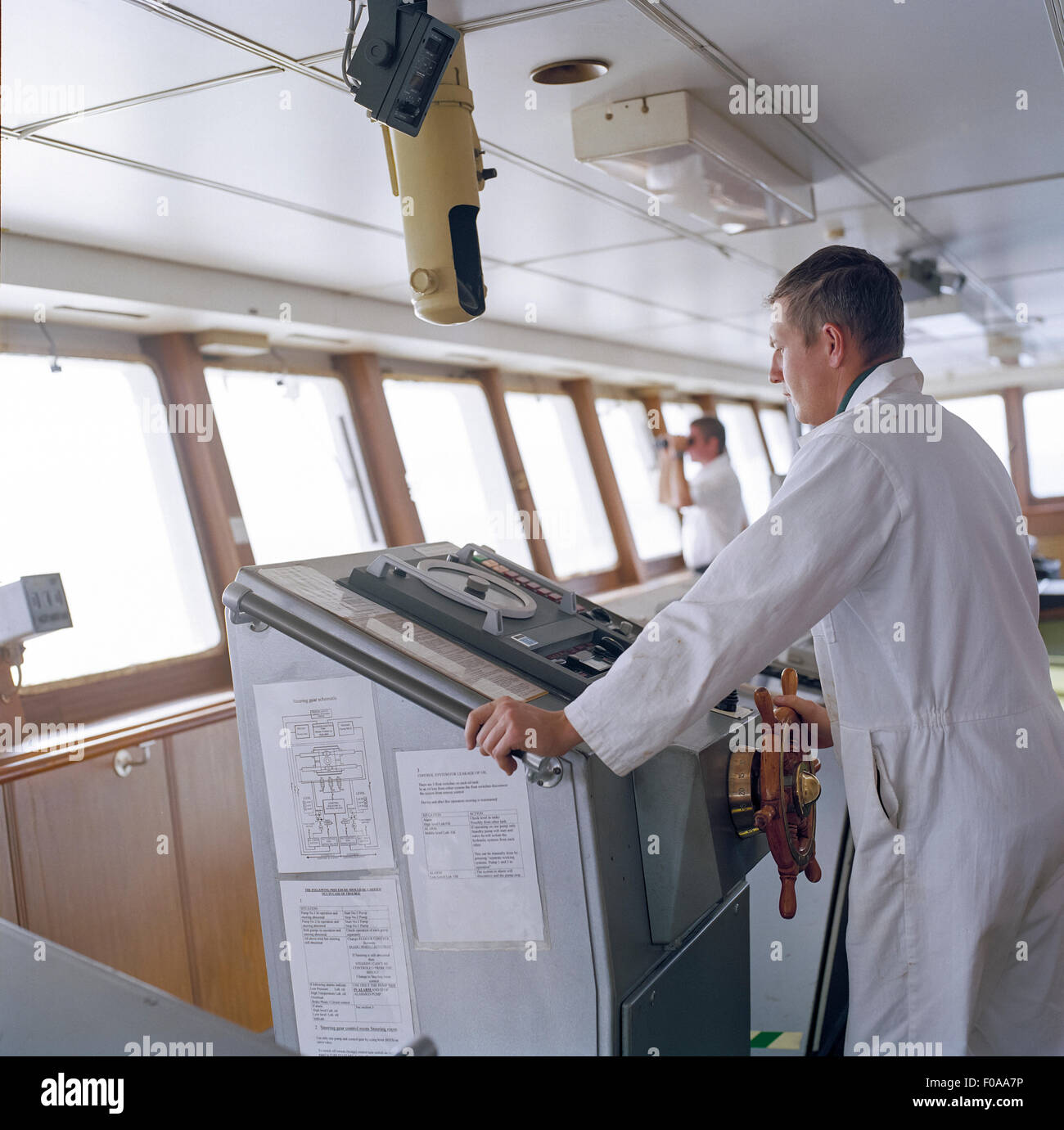 Sailor on bridge steering container ship at sea - Stock Image