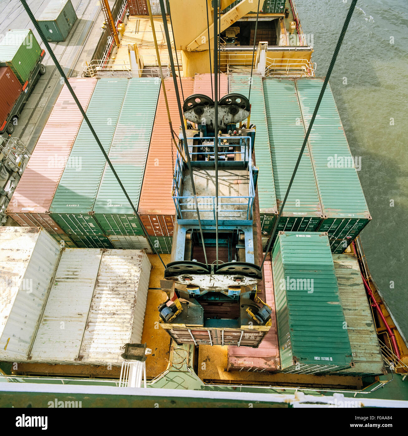 Shipping container being lowered by crane onto ship in port, high angle view - Stock Image