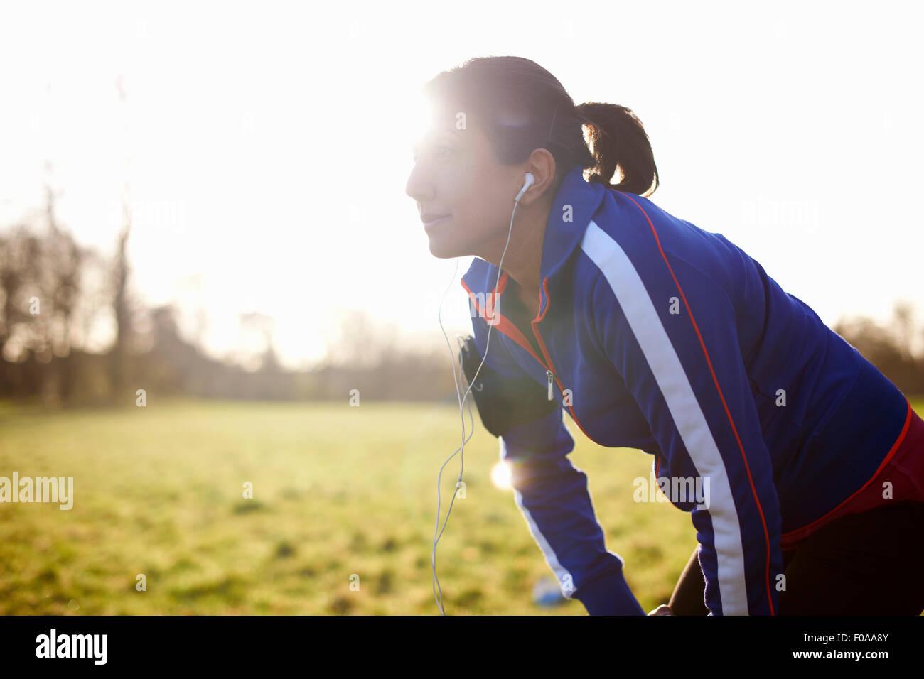 Mature female runner in field taking a break - Stock Image