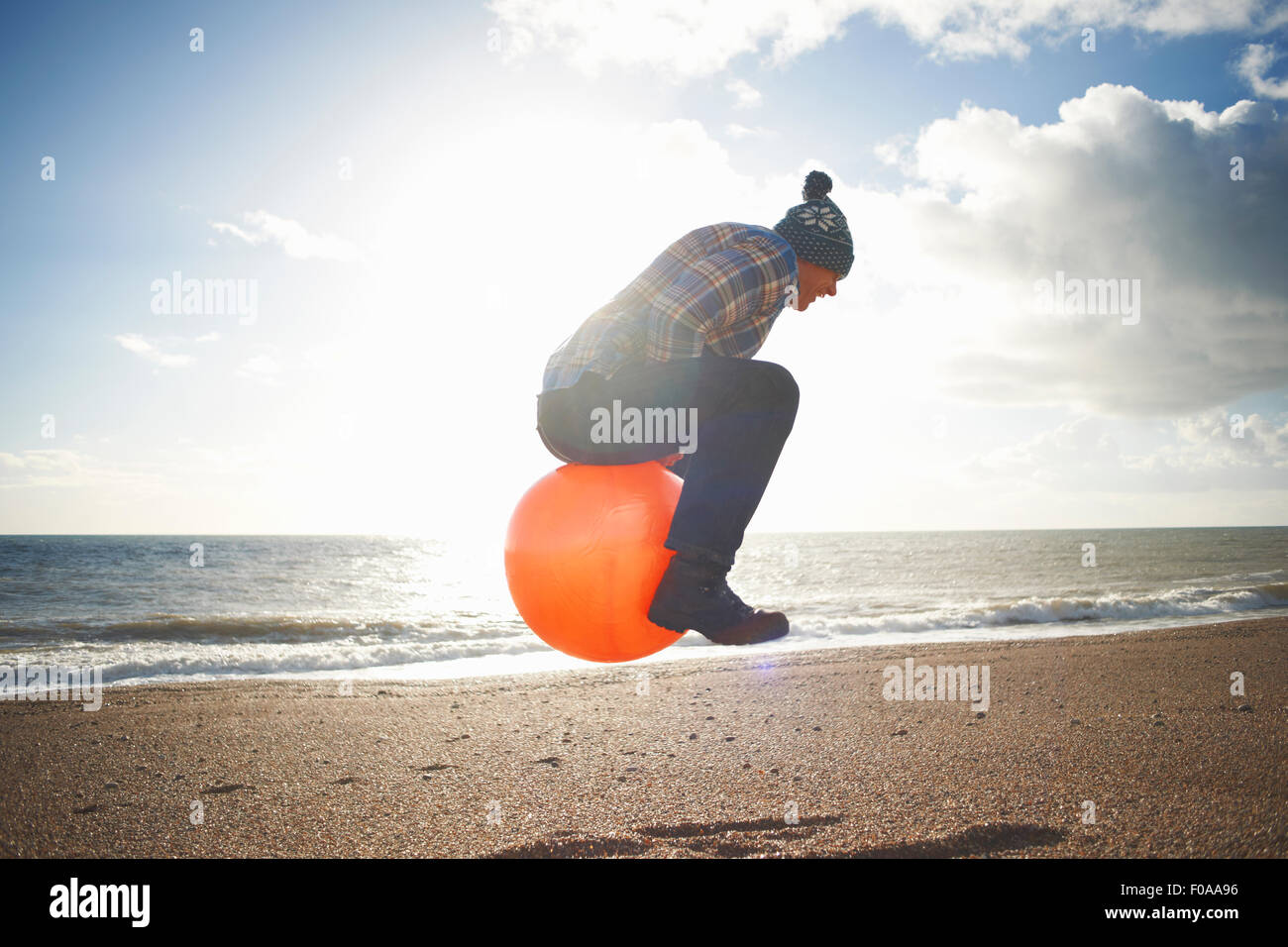 Mature man jumping mid air on inflatable hopper at beach - Stock Image