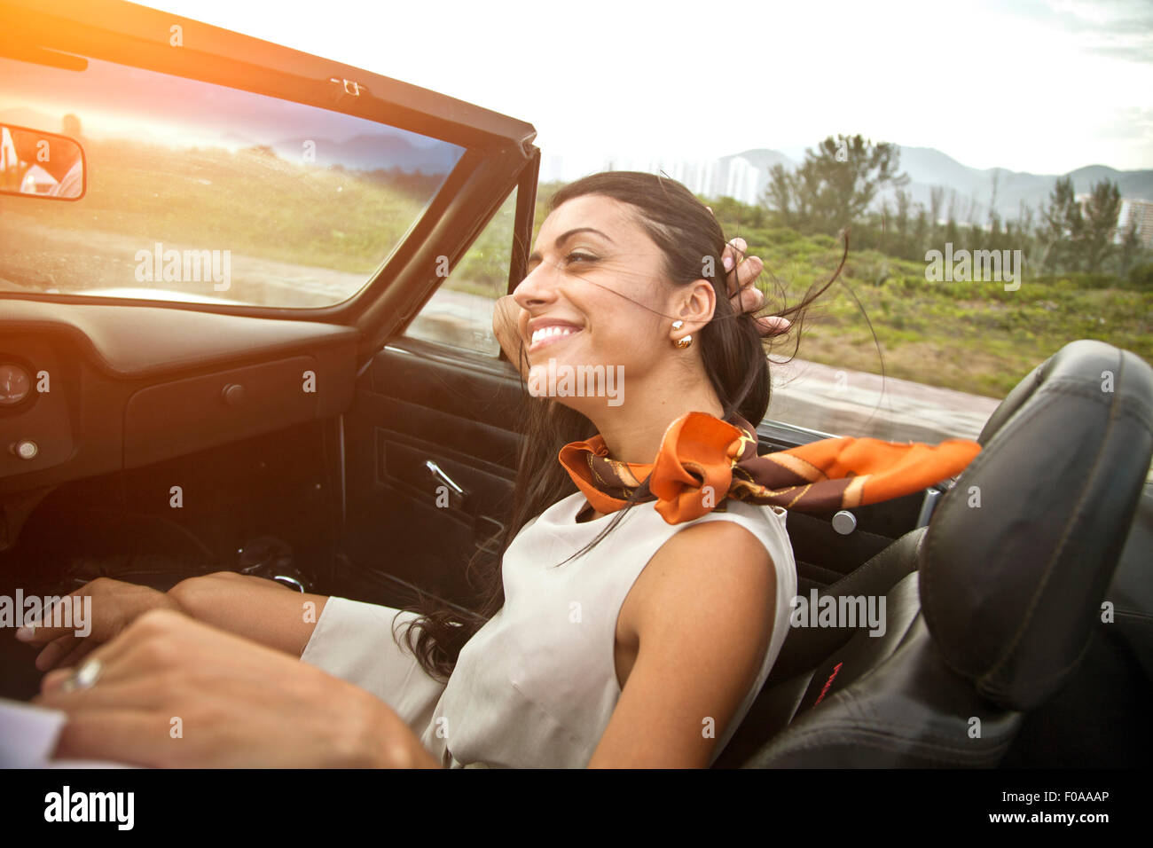 Mid adult woman in passenger seat of convertible car - Stock Image