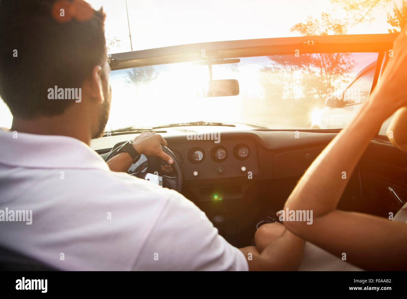 Mid adult couple in convertible car, rear view, close-up - Stock Image