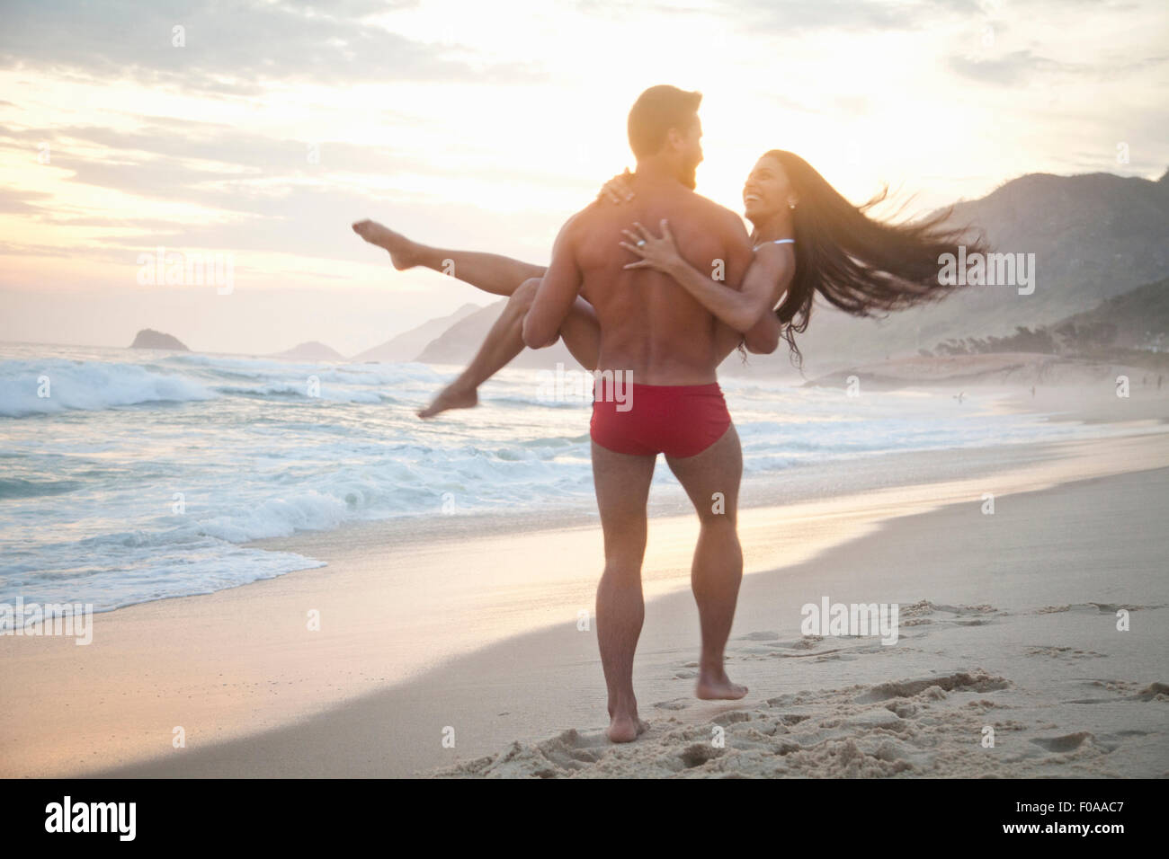 Mid adult couple on beach,man carrying woman in arms, rear view Stock Photo