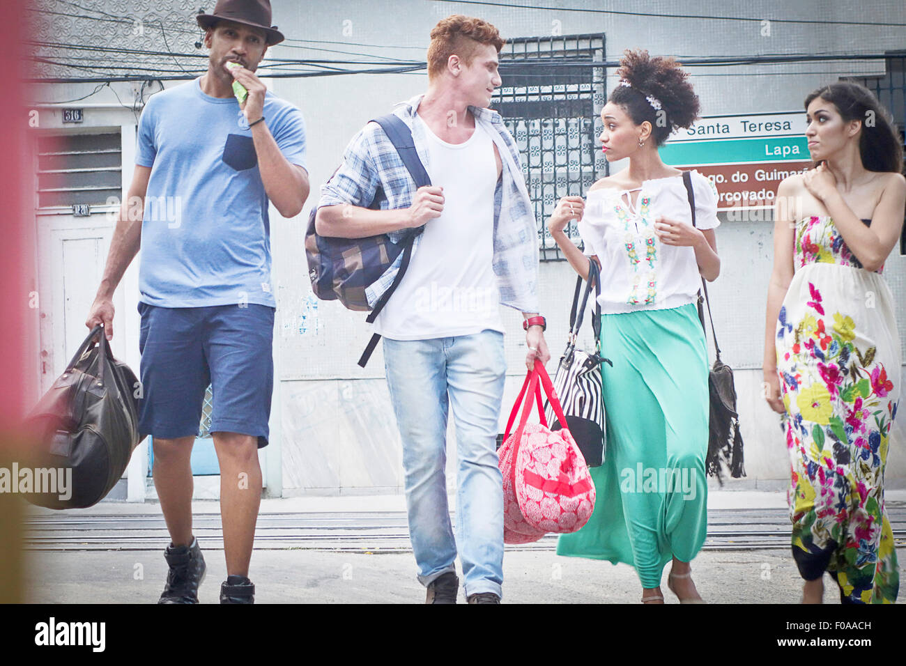 Small group of people walking together, carrying travel bags - Stock Image