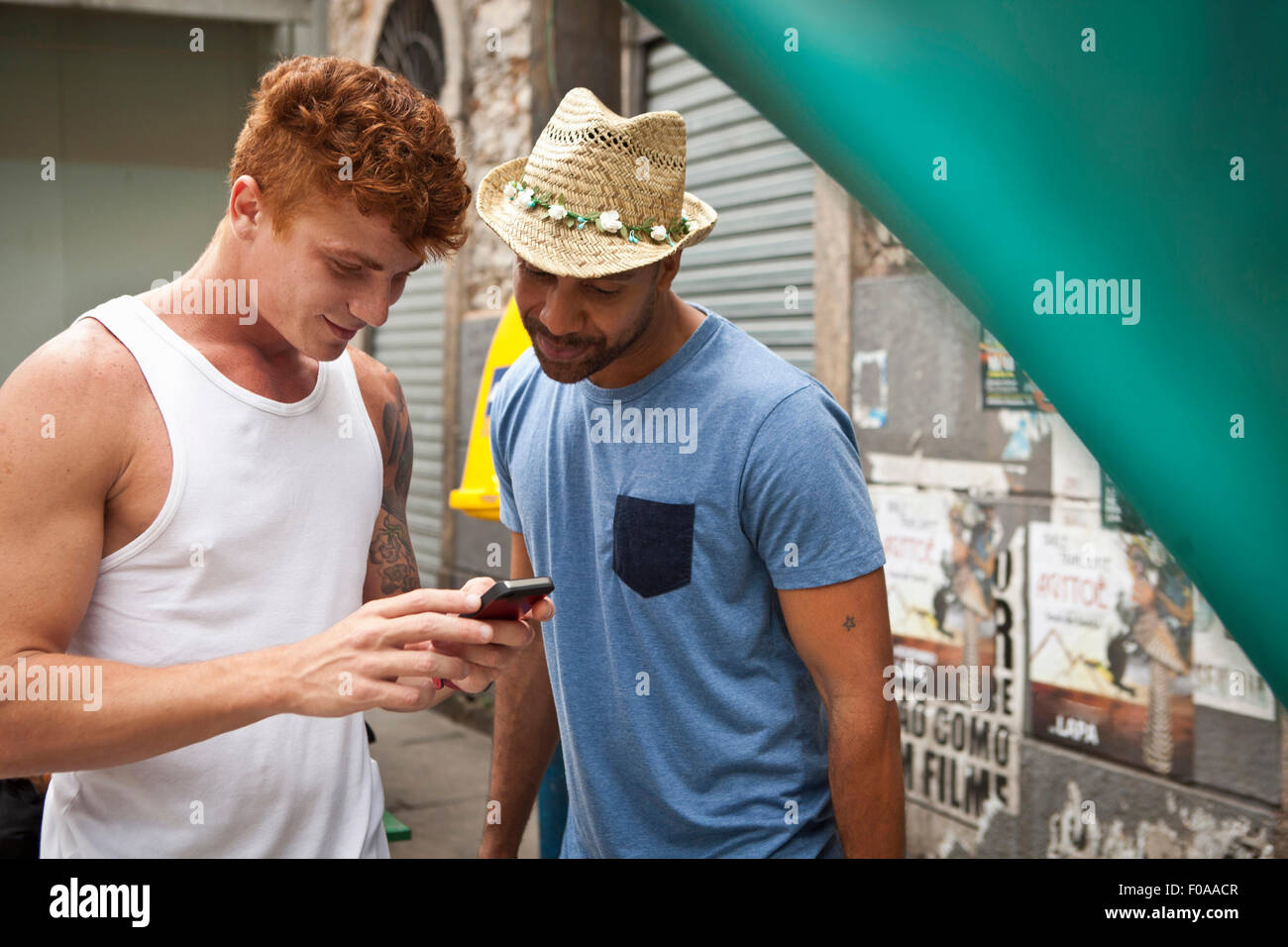 Two male friends looking at smartphone together Stock Photo