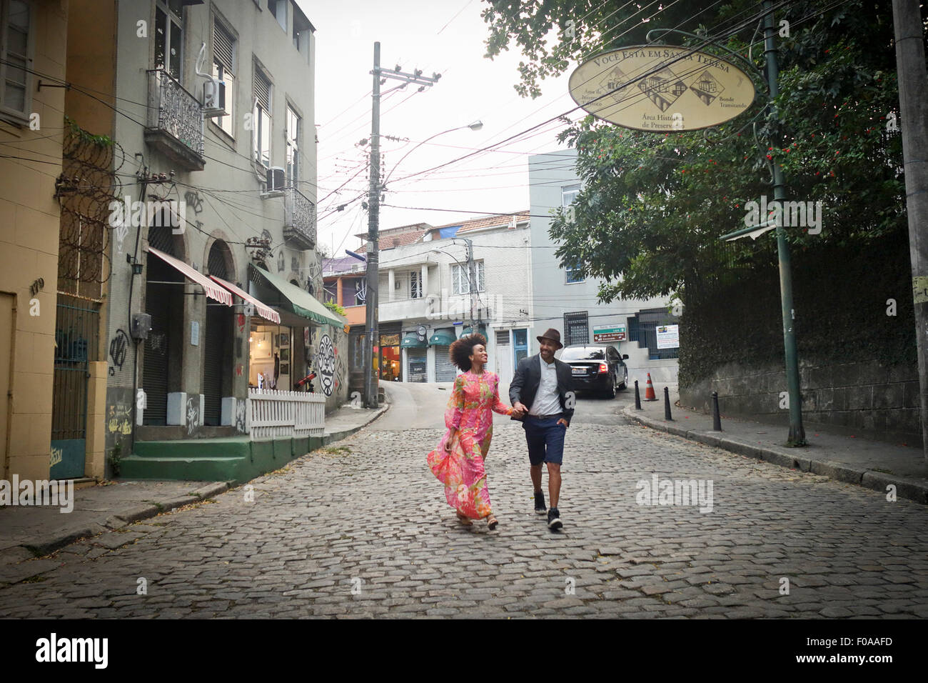 Couple walking down cobbled street, hand in hand - Stock Image