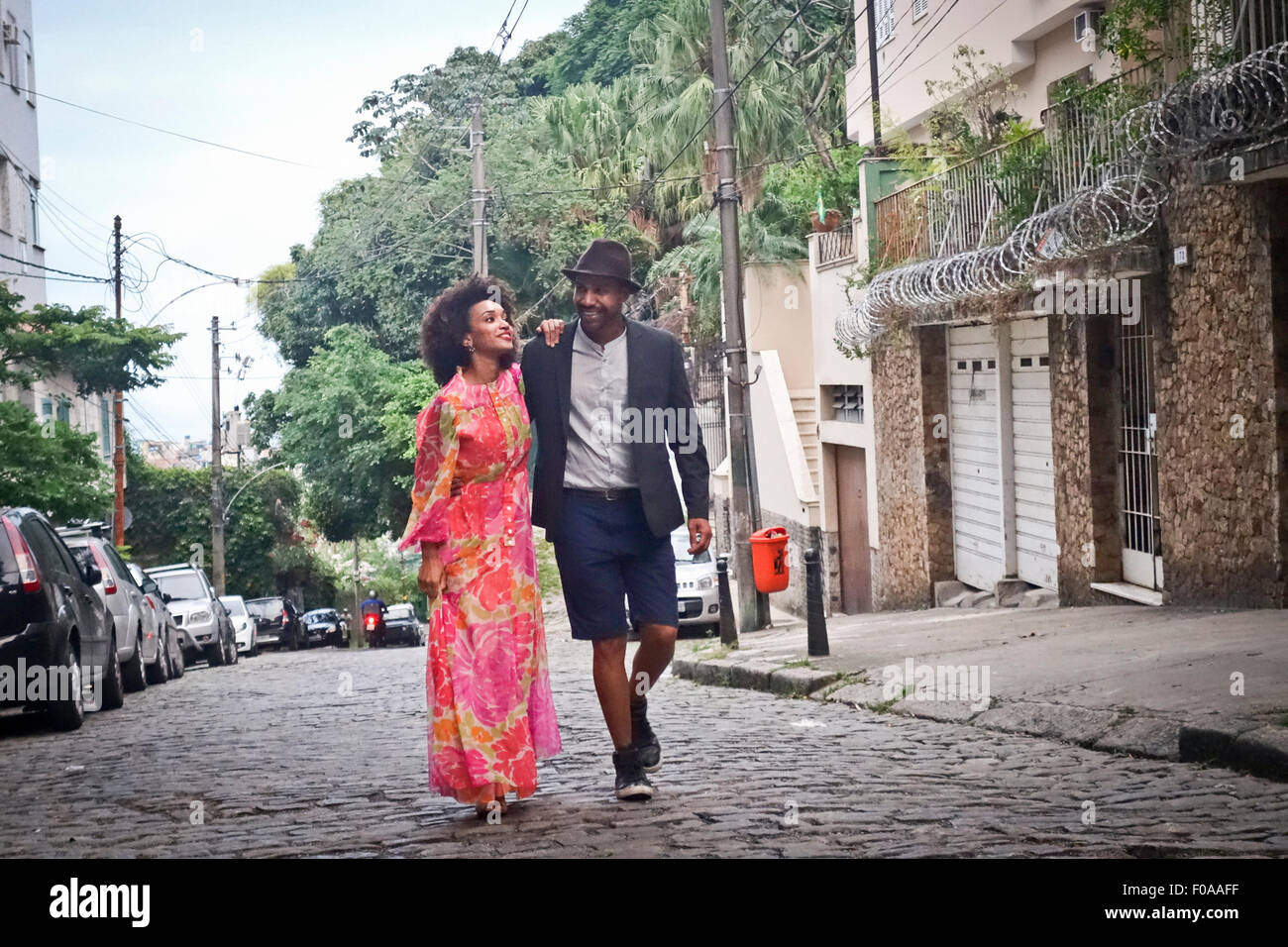 Couple walking down cobbled street, smiling - Stock Image