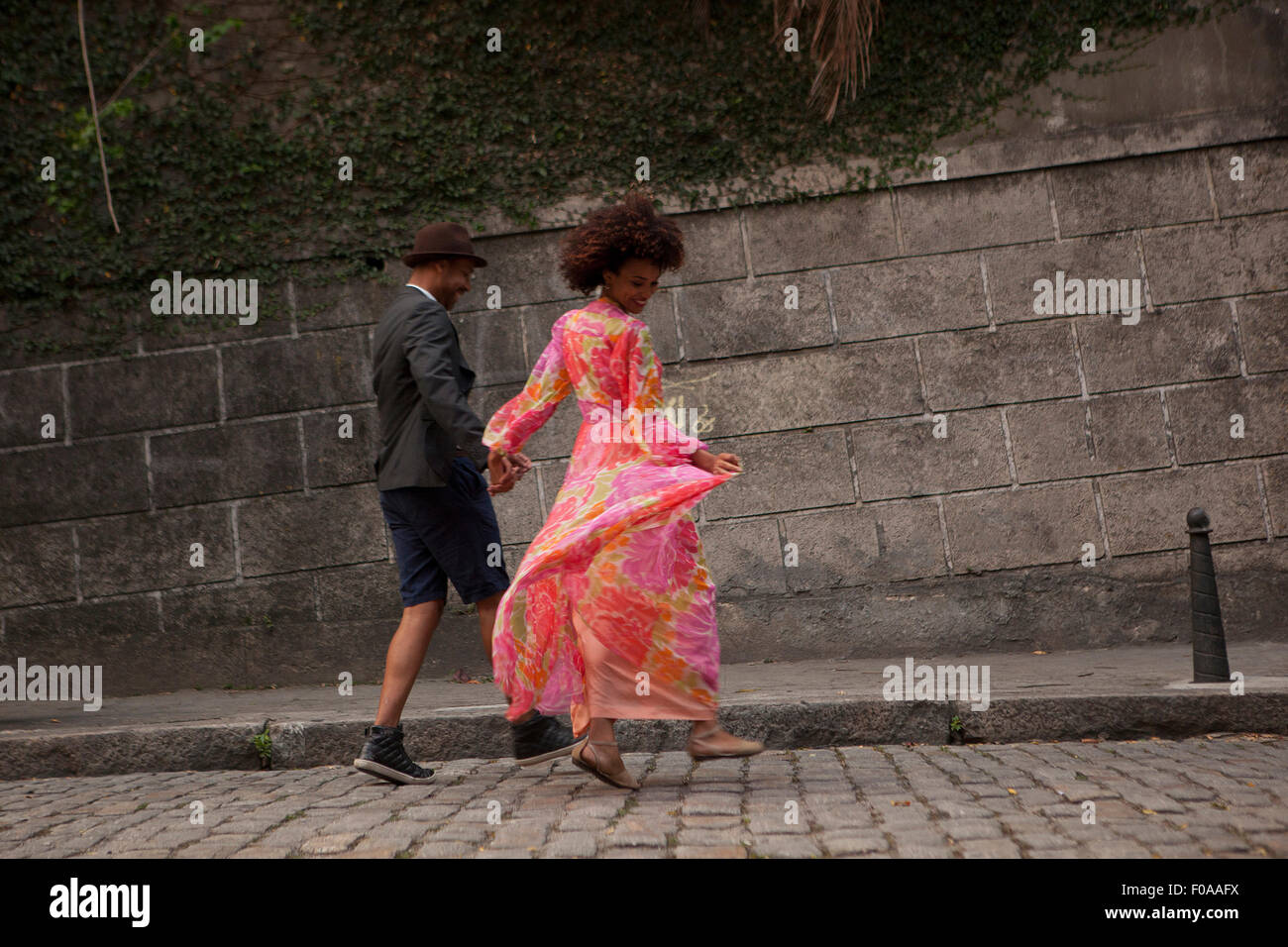 Couple walking along cobbled street, rear view - Stock Image