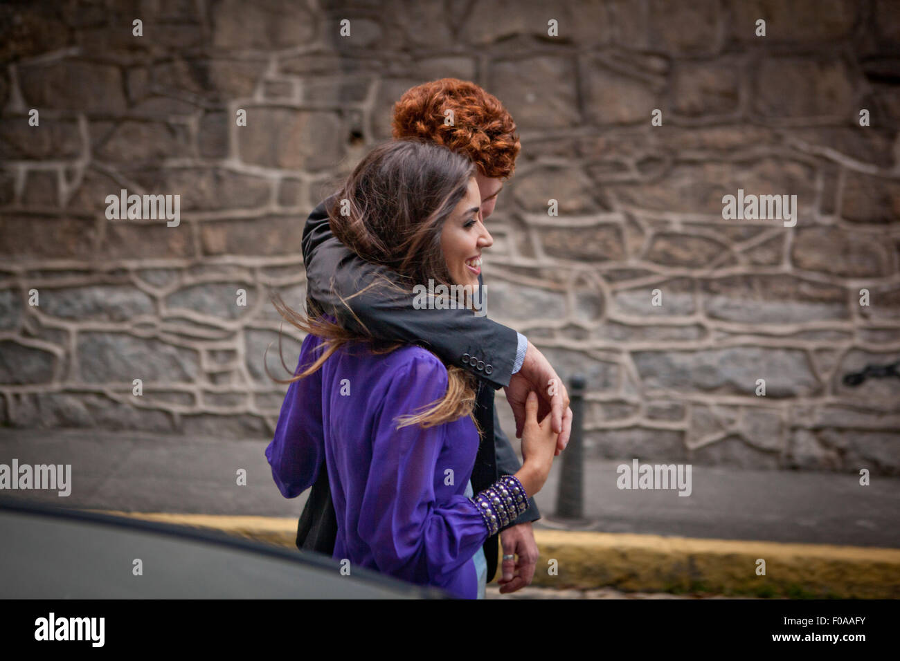 Couple walking along street, arms around each other - Stock Image