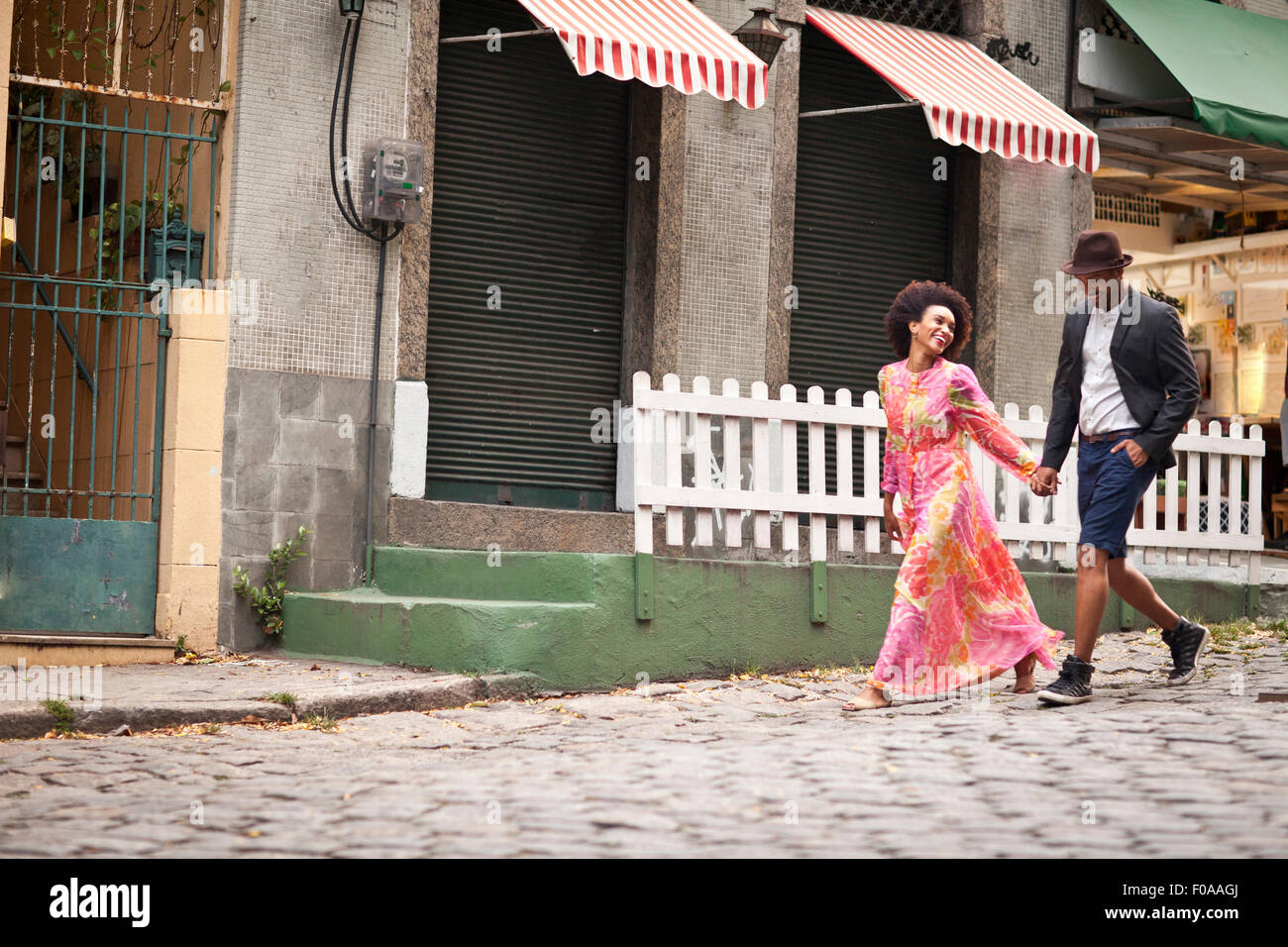 Couple walking along cobbled street, hand in hand - Stock Image