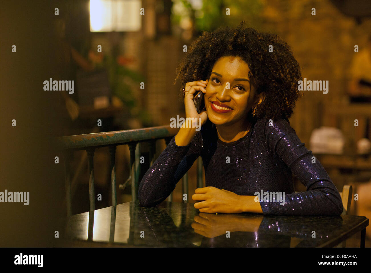 Young woman sitting at table at bar, using mobile phone - Stock Image