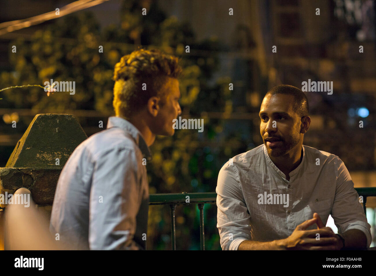 Two men sitting at table at bar, talking - Stock Image