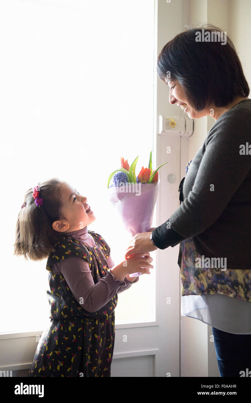 Young girl giving mother flowers - Stock Image
