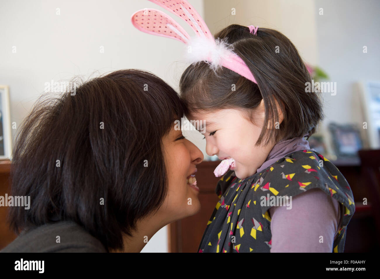 Mother and daughter, face to face, daughter wearing bunny ears and holding sweet in her mouth - Stock Image