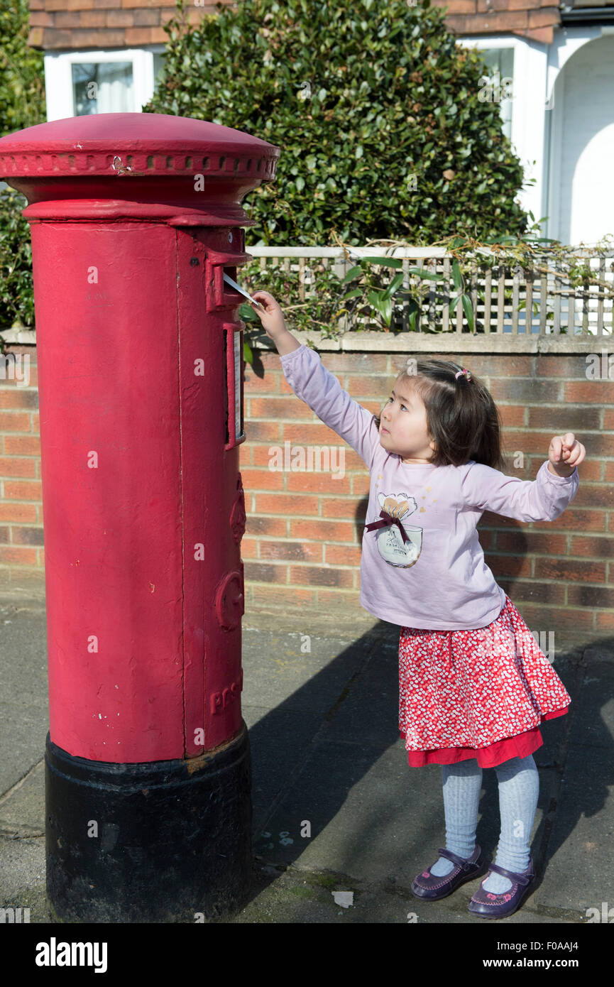 Young girl at post box, reaching up to post letter - Stock Image