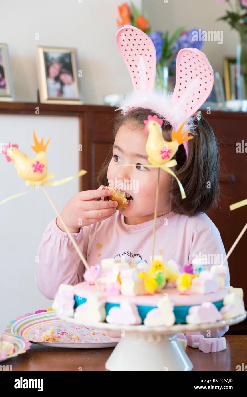 Young girl wearing bunny ears, eating cake - Stock Image