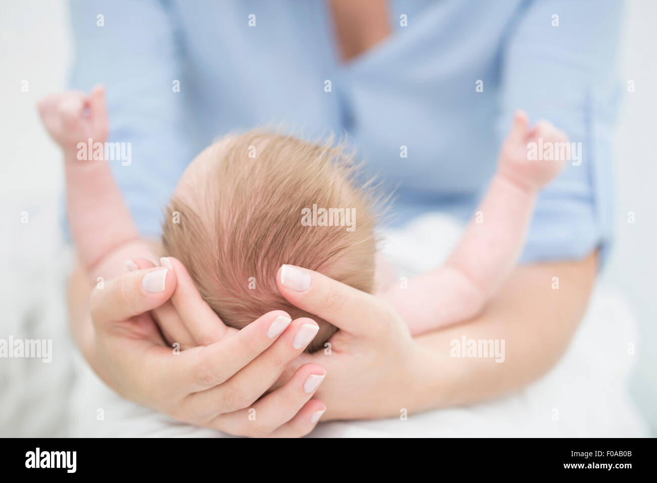 Mother cradling baby in arms - Stock Image