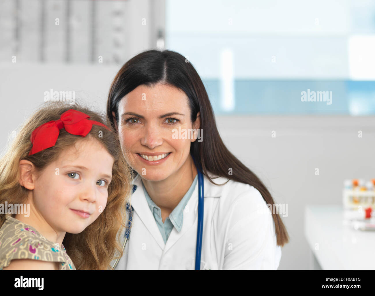 Doctor bonding with young girl during consultation - Stock Image