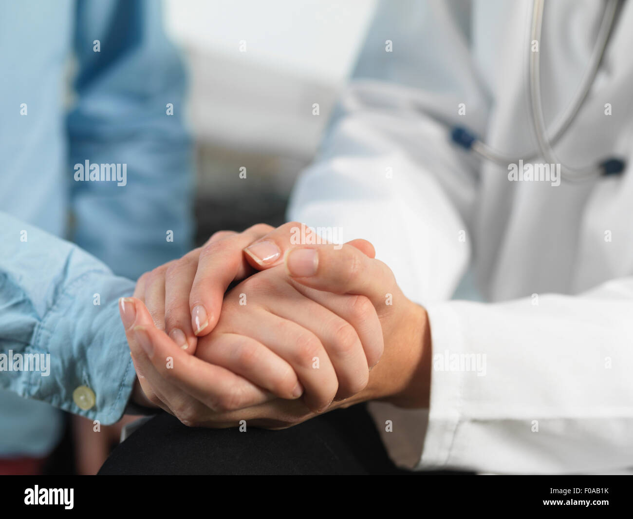 Doctor comforting young boy in clinic - Stock Image