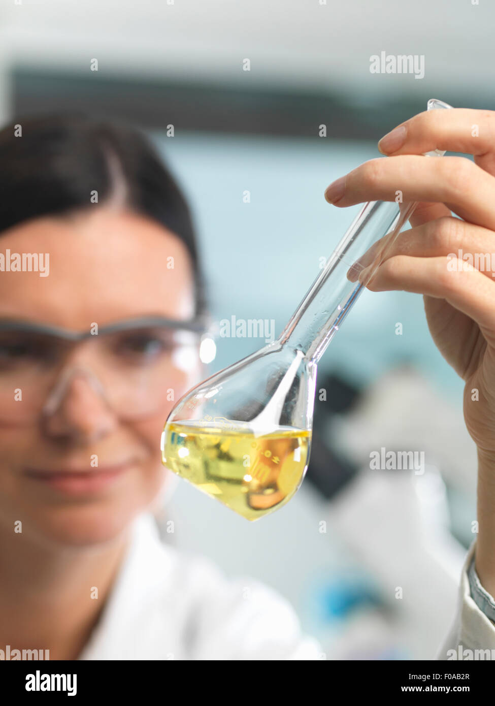 Chemist looking at solution in flask during research experiment - Stock Image