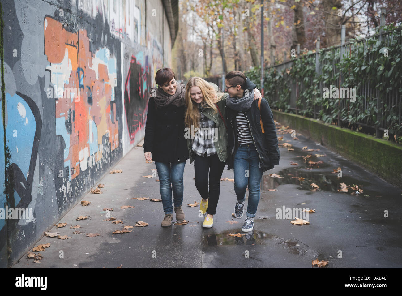 Three sisters walking by graffiti wall - Stock Image
