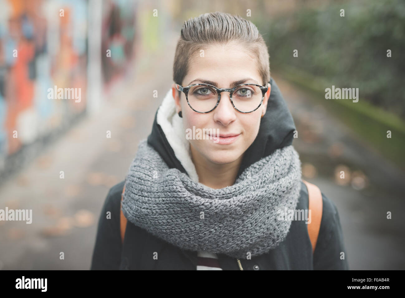 Teenager on street, graffiti wall in background - Stock Image