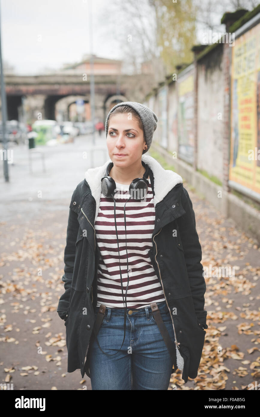 Teenager with headphones on street - Stock Image