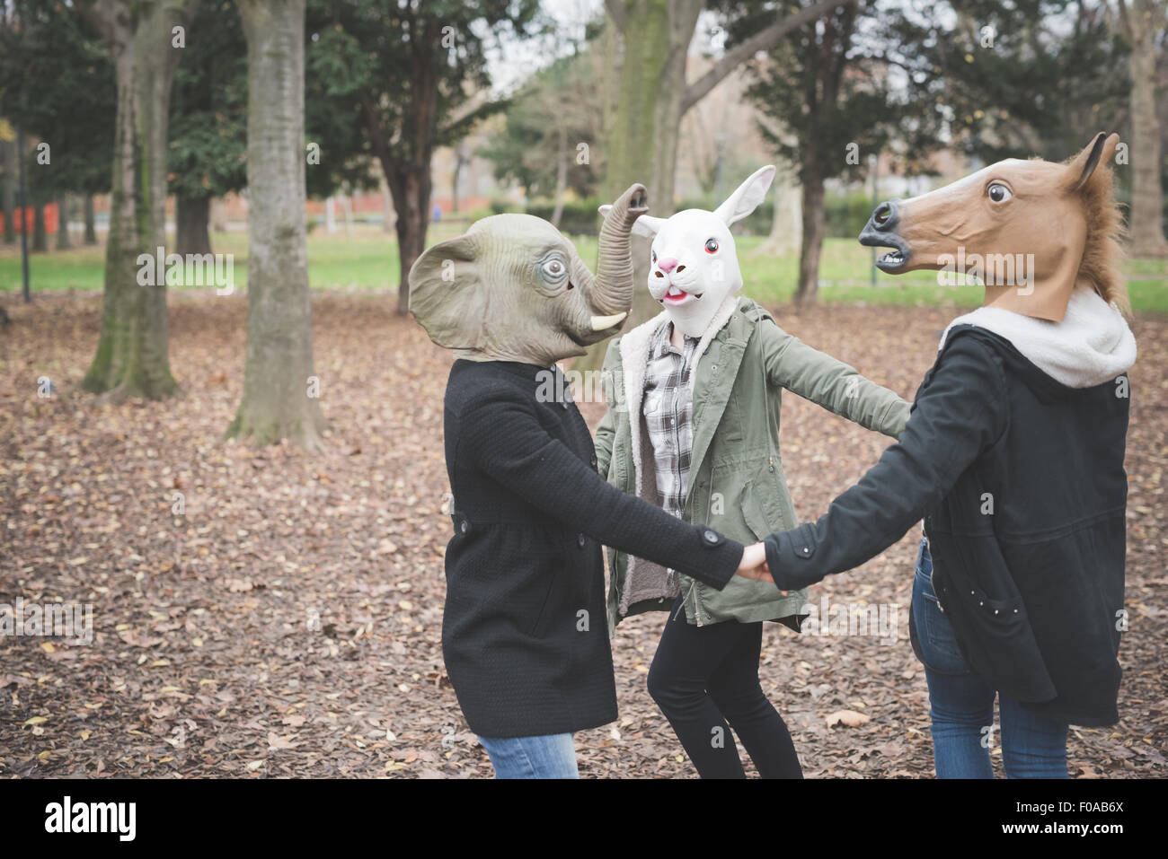Three sisters wearing animal masks dancing in park - Stock Image