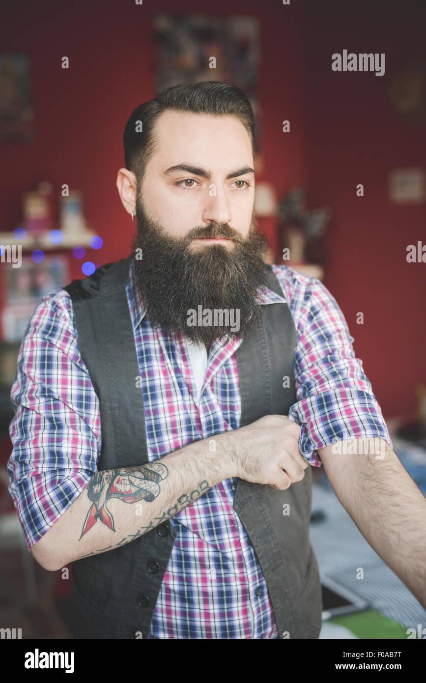 Young bearded man folding shirt sleeve - Stock Image