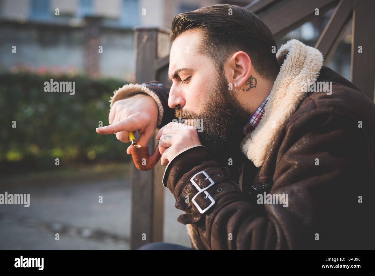 Young bearded man smoking pipe on steps - Stock Image
