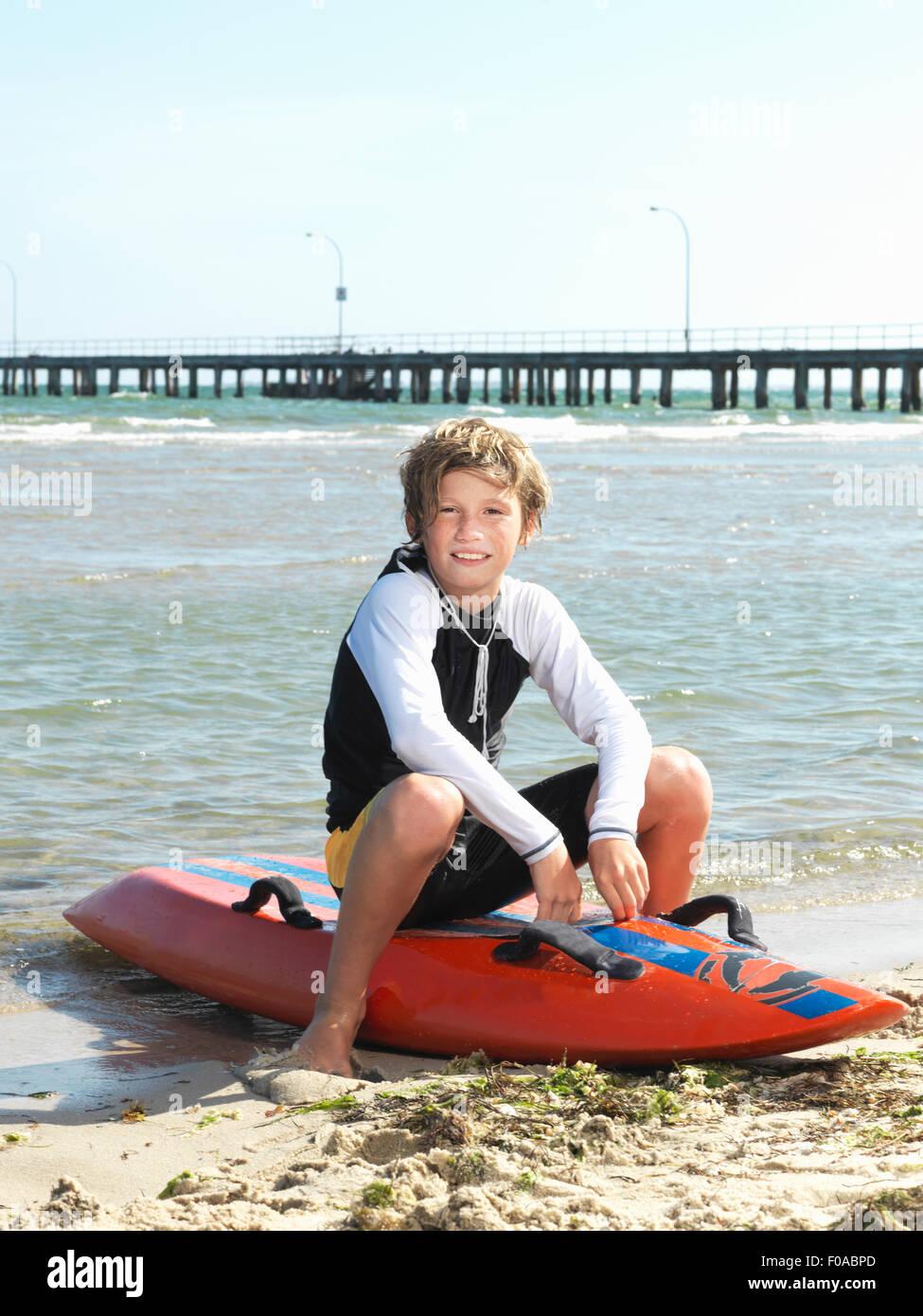 Portrait of boy nipper (child surf life savers) sitting on surfboard, Altona, Melbourne, Australia - Stock Image