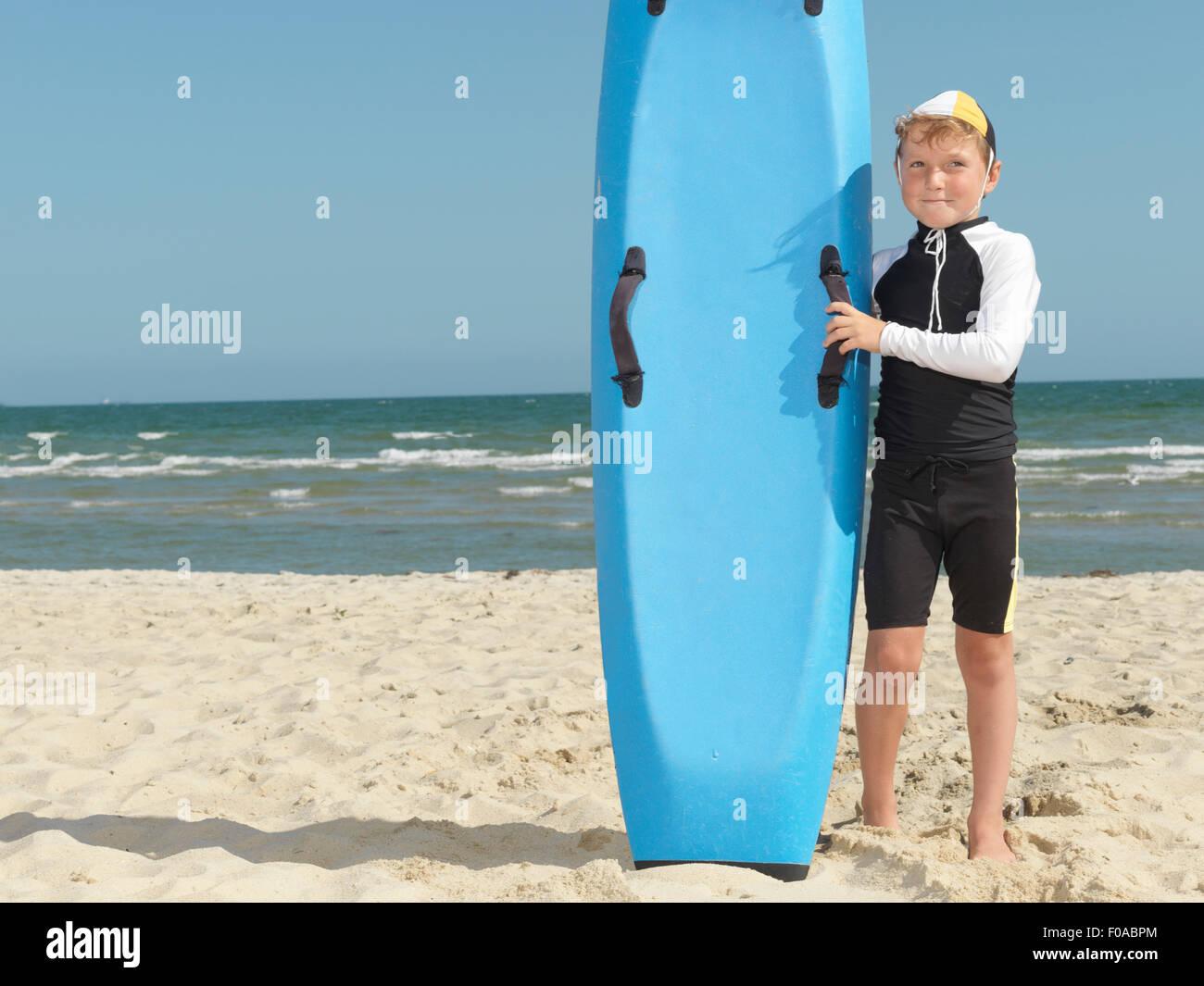 Portrait of boy nipper (child surf life savers) next to surfboard, Altona, Melbourne, Australia - Stock Image