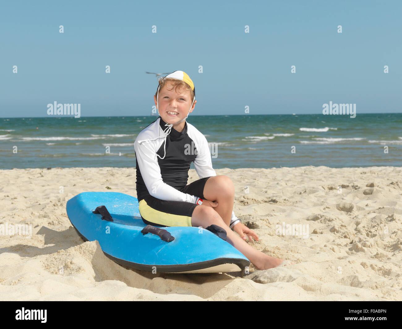 Portrait of boy nipper (child surf life savers) on surfboard at beach, Altona, Melbourne, Australia - Stock Image