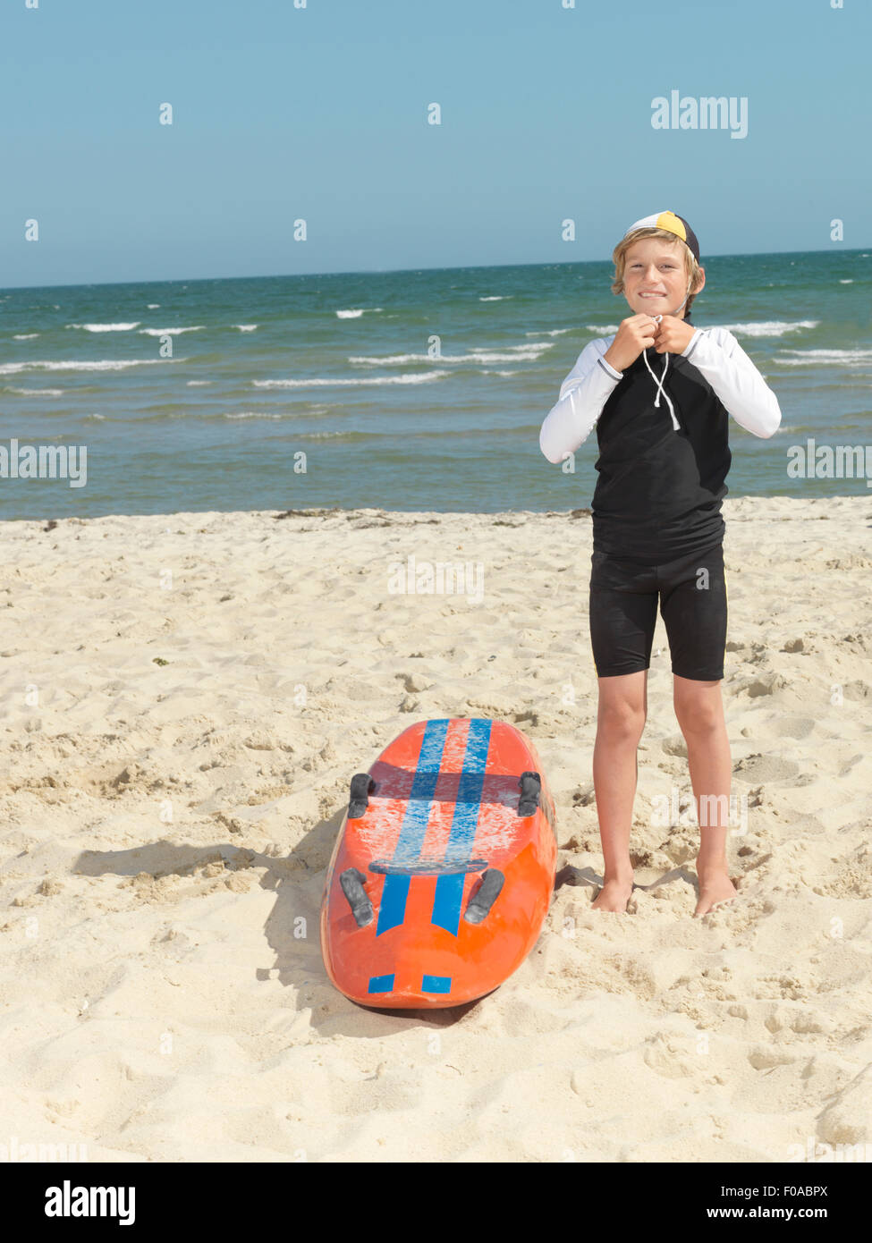 Portrait of boy nipper (child surf life savers) fastening cap, Altona, Melbourne, Australia - Stock Image