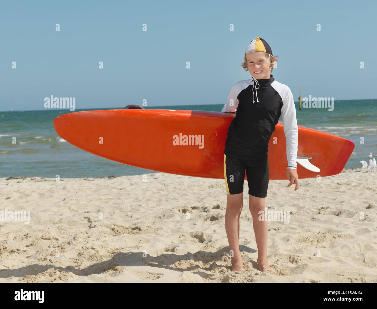 Portrait of confident boy nipper (child surf life savers) carrying surfboard, Altona, Melbourne, Australia - Stock Image