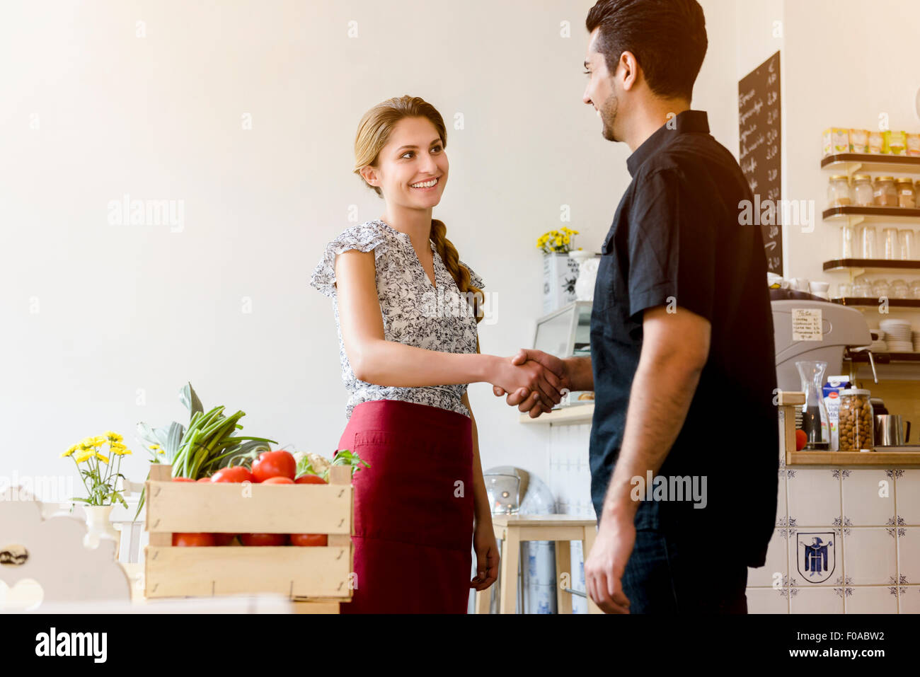 Young woman shaking mans hand - Stock Image