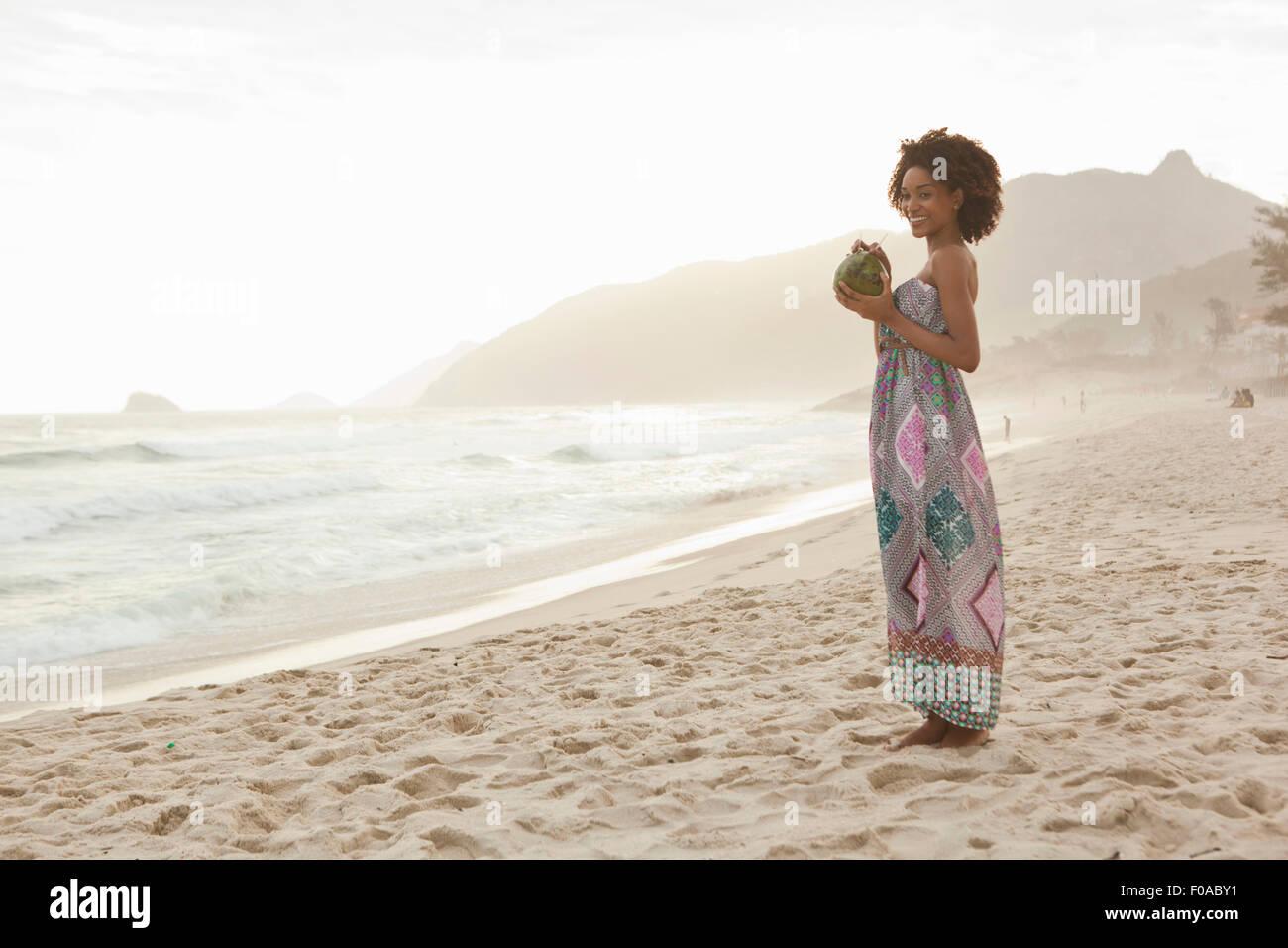 Young woman drinking coconut milk on beach, Rio De Janeiro, Brazil - Stock Image