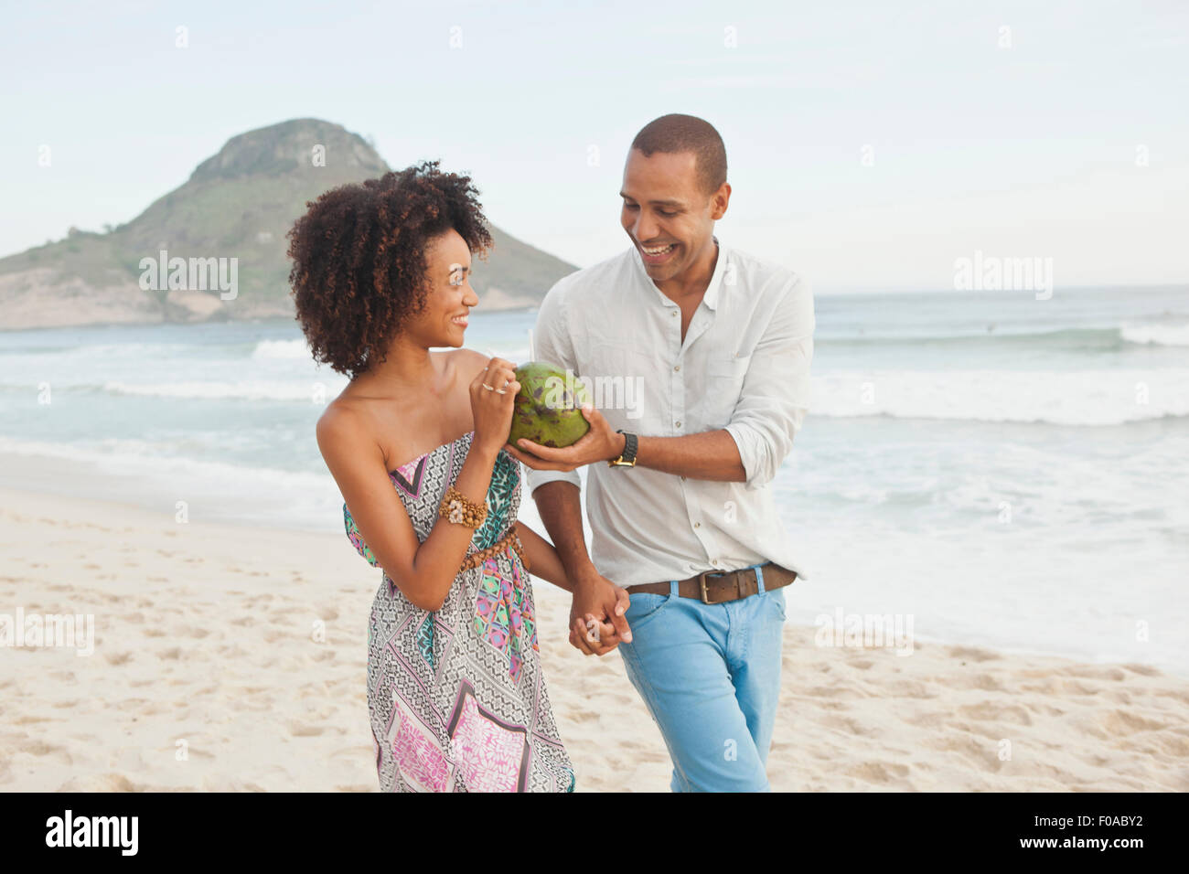Couple drinking coconut milk on beach, Rio De Janeiro, Brazil - Stock Image