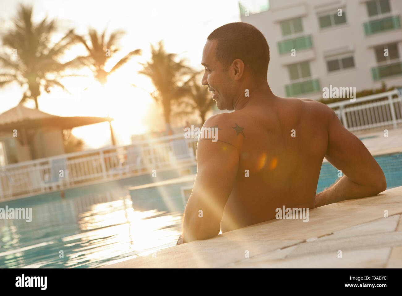 Rear view of mid adult man standing in sunlit hotel swimming pool, Rio De Janeiro, Brazil - Stock Image