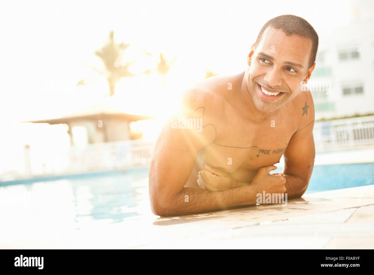 Mid adult man standing in sunlit hotel swimming pool, Rio De Janeiro, Brazil - Stock Image