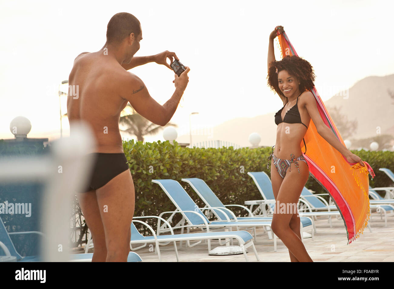 Young woman being photographed by boyfriend at hotel poolside, Rio De Janeiro, Brazil - Stock Image