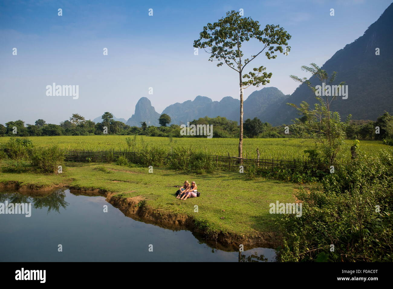 Two female friends relaxing on Nam Song riverbank, Vang Vieng, Laos - Stock Image