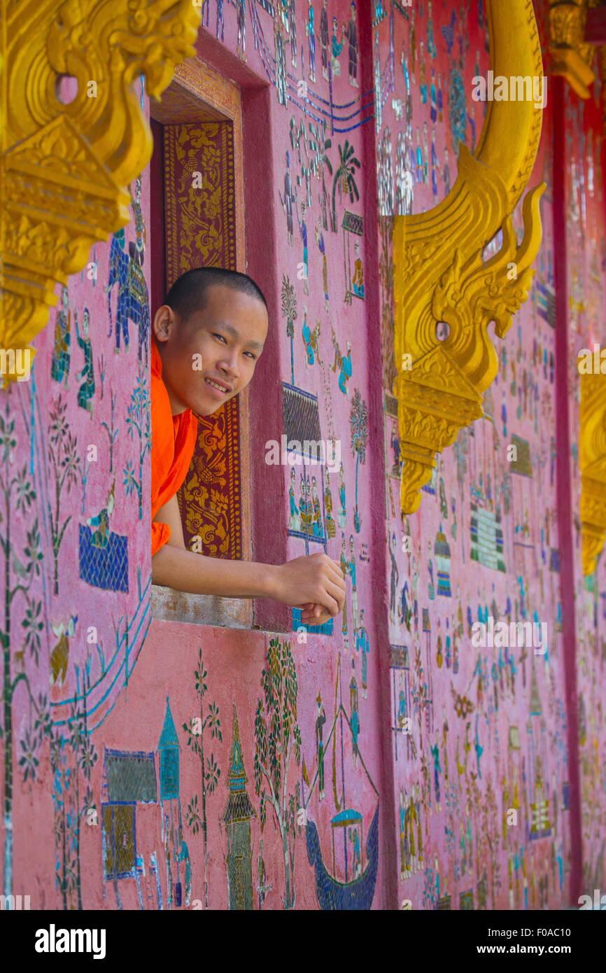 Buddhist monk looking out of Wat Xieng Thong window, Luang Prabang, Laos - Stock Image